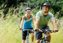Pár na kole projíždí krajinou s rákosím
